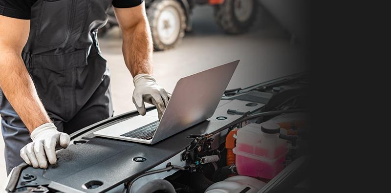Mechanik diagnozujący auto zapomocą laptopa